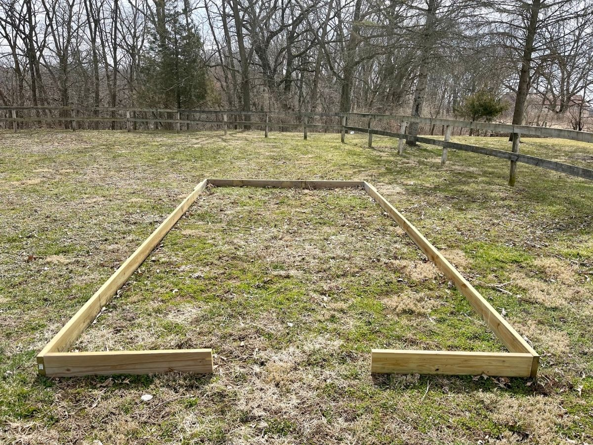 Wooden greenhouse stabilizer frame on grass
