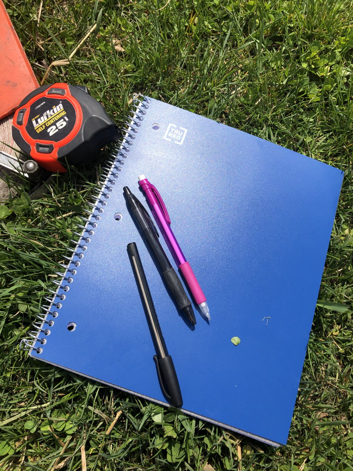 A notebook, pens, and measuring tape for garden planning