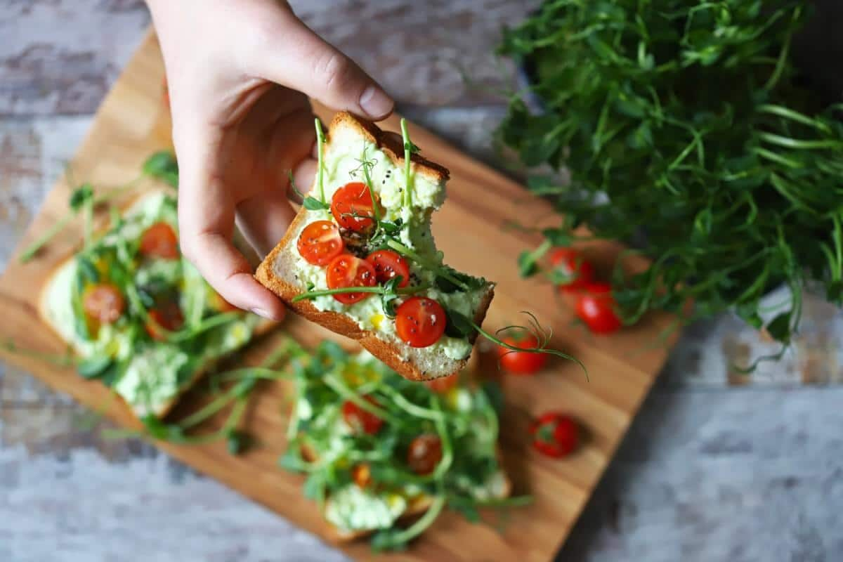 A hand holding a piece of bread with tomatoes and microgreens on it.