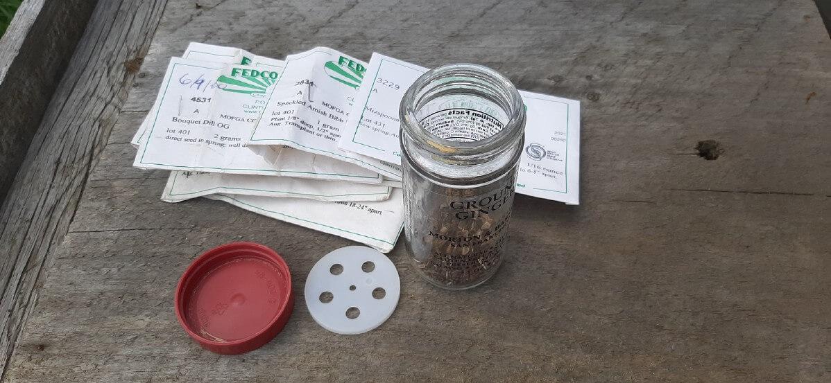 Assortment of garden seeds and a glass jar to mix them.