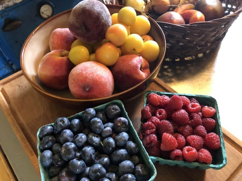bowl of fresh fruit and containers of fresh blueberries and raspberries